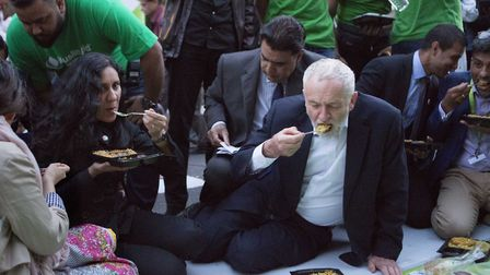 Leader of the Labour Party Jeremy Corbyn joins supporters as he sits and eats at a street iftar to c