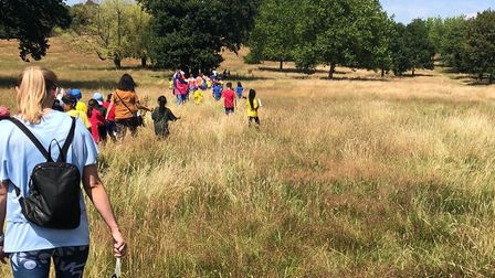 Children tackling the long grass on the way to their sports day.