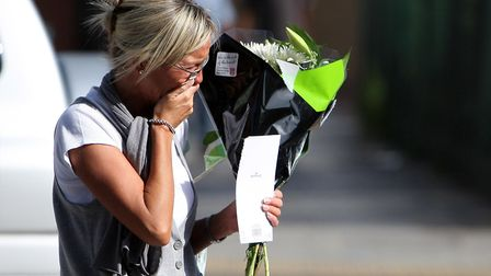 A mourner arrives to lay flowers at the scene of Ben Kinsella's murder in 2008. Picture: Dominic Lip