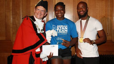 Mayor of Islington Cllr Dave Poyser, left, and Reuben Arthur, right, present Tomique Gibson with her