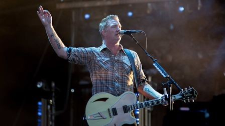 Josh Homme of the Queen's of the Stage raises his guitar pick aloft. Photo: Michelle Roberts