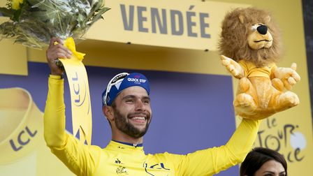 Quick Step Floors's Fernando Gaviria celebrates on the podium after taking the yellow jersey and win
