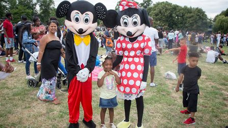 Cataleah Worrell, 5, with Mickey and Minnie at Quamari's One Love Memorial Festival in Harlesden (Pi