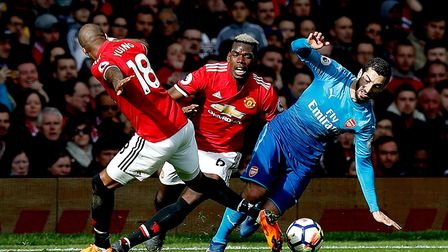 Manchester United's Paul Pogba (centre) and Ashley Young (left) battle for the ball with Arsenal's H