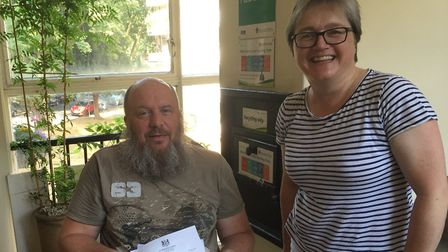 Wheelchair-bound Fergus Johnston and Cllr Caroline Russell pose with letters from the DWP and Downin