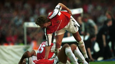 A dejected Thierry Henry of Arsenal is consoled by Tony Adams after the dramatic late defeat to Live