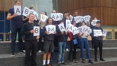 City of London Academy Highbury Grove students hold up cards with their marks on, on A Level Results