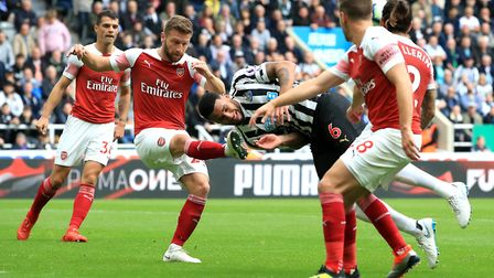 Arsenal's Shkodran Mustafi (left) and Newcastle United's Jamaal Lascelles (centre) battle for the ba