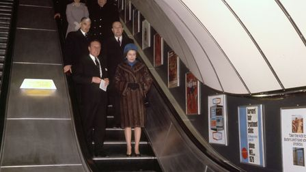 The Queen travelling down the escalator at Green Park Underground station as she opens the new secti