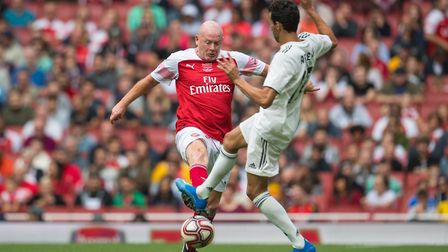 Arsenal Legends' Perry Groves (left) and Real Madrid Legends' Alvaro Arbeloa battle for the ball dur