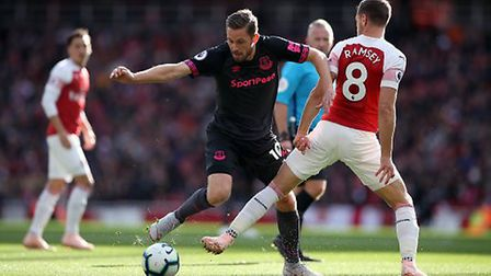 Everton's Gylfi Sigurdsson and Arsenal's Aaron Ramsey (right) battle for the ball during the Premier