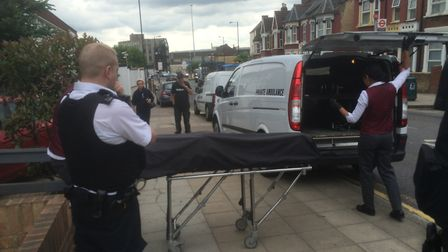 A body is removed from the house in Neasden Lane where a young woman died this morning. Picture: Luc