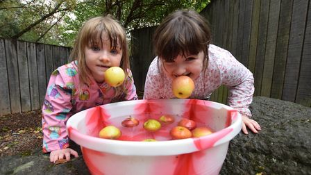 Apple bobbing with sisters Nicola-Rose, six, and Sophie-May Burdett-Rowan, eight. Picture: Polly Han
