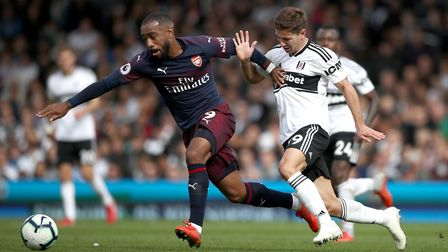 Arsenal's Alexandre Lacazette (left) and Fulham's Luciano Vietto battle for the ball during the Prem