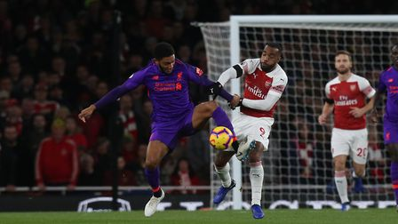 Joe Gomez of Liverpool sheilds the ball from Alexandre Lacazette of Arsenal in the Premier League ga