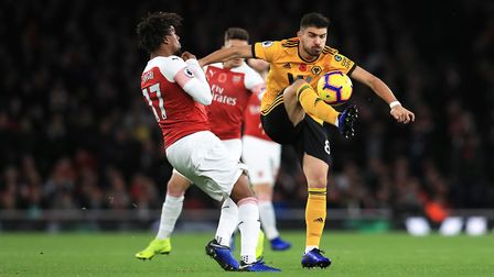Arsenal's Alex Iwobi (left) and Wolverhampton Wanderers' Ruben Neves battle for the ball. PA