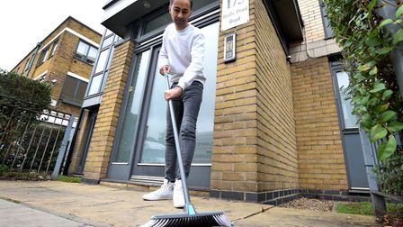 Arfan Qureshi sweeps his doorstep, where a teenager took a 'dump'. Picture: Polly Hancock