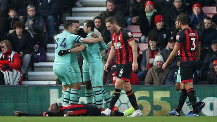 Bournemouth's Jefferson Lerma lays dejected after conceding an own goal as Arsenal players celebrate
