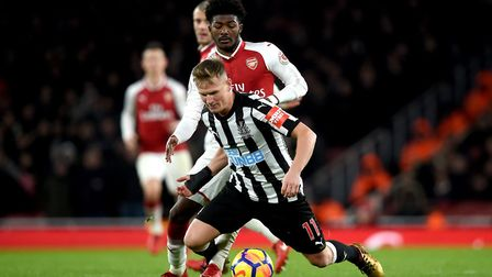 Arsenal's Ainsley Maitland-Niles (back) and Newcastle United's Matt Ritchie battle for the ball duri