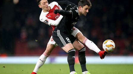 Arsenal's Mesut Ozil (left) and Qarabag's Miguel Michel battle for the ball during the UEFA Europa L