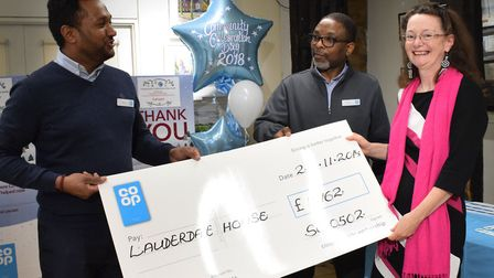 Lauderdale House director Katherine Ives collects a cheque from local Co-op store managers Sai Thava