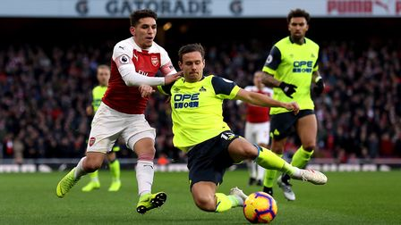 Arsenal's Lucas Torreira (left) and Huddersfield Town's Chris Lowe battle for the ball during the Pr
