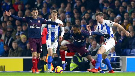 Arsenal's Alexandre Lacazette (centre) battles for the ball with Brighton & Hove Albion's Dale Steph