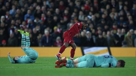 Georginio Wijnaldum of Liverpool has the ball with two Arsenal players down in the Premier League g