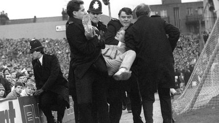 Police handle a fan who has been pulled out of the crowd at the start of the match.