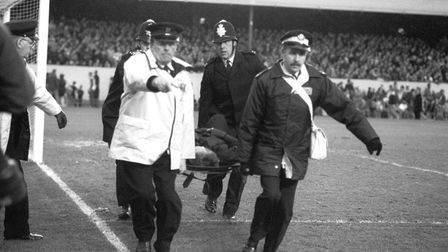 An injured Policeman is stretchered away following crowd violence ahead of kick-off.
