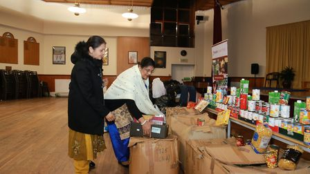 Devotees of Neasden Temple bringing in clothes and food for distribution to homeless