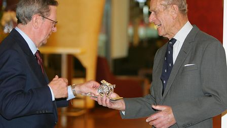 Arsenal Chairman Peter Hill-Wood (L) presents Britain's Prince Philip with a gift as he officially o