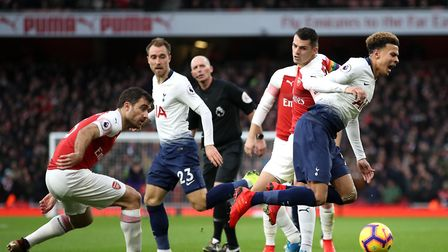 Tottenham Hotspur's Dele Alli (right) is caught by Arsenal's Granit Xhaka during the Premier League