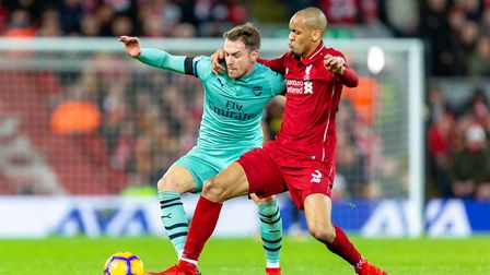 Aaron Ramsey of Arsenal holds off a tackle from Fabinho of Liverpool in the Premier League game betw