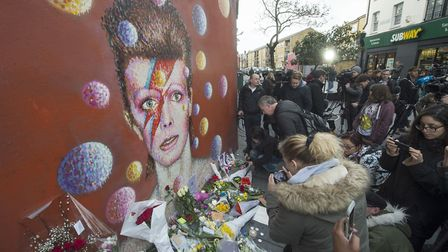 A woman with her face painted as Ziggy Stardust by a mural of David Bowie on the wall of a Morley's