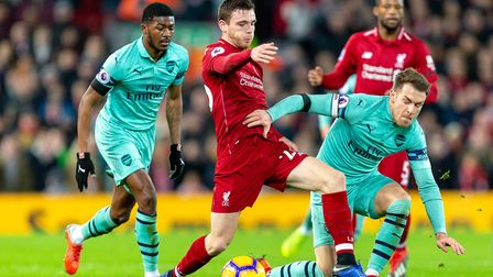 Andrew Robertson of Liverpool on the ball under pressure from Ainsley Maitland-Niles and Aaron Ramse