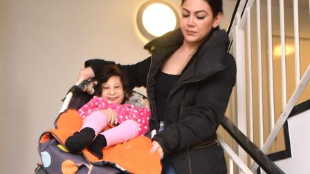Jeyda Yusuf carries daughter Aaliyah (12) down the stairs of Papyrus House. She walks her other daug