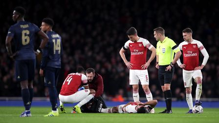 Arsenal's Sokratis Papastathopoulos (floor) lies injured before being substituted during the FA Cup
