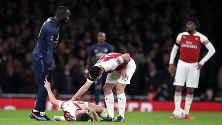Arsenal's Laurent Koscielny (floor) lies injured as Granit Xhaka consoles him after a collision with