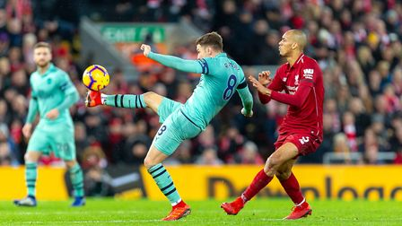 Aaron Ramsey of Arsenal hooks a ball forward under pressure from Fabinho of Liverpool in the Premier
