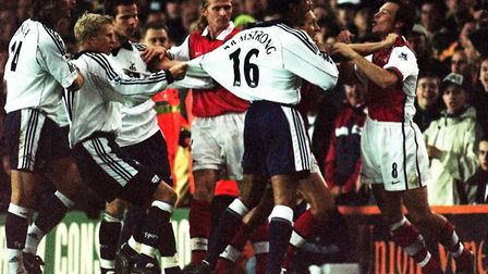 Arsenal 's Freddie Ljungberg (right) is restrained by a team mate after fouling Tottenham Hotspur 's