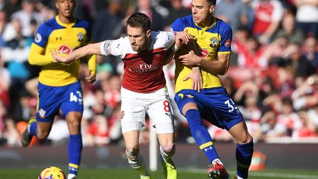 Arsenal's Aaron Ramsey and Southampton's Jan Bednarek battle for the ball during the Premier League