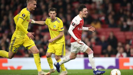 Arsenal's Mesut Ozil (right) appears dejected after failing to collect the ball