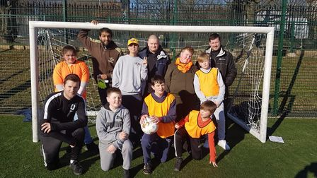 Youngsters face the camera at a come and play disability football session.