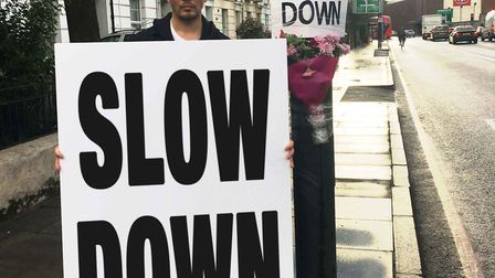 Morgan Penn with his sign and the flowers, which he put up to stop bus drivers speeding.