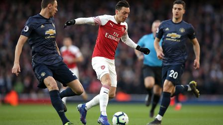 Arsenal's Mesut Ozil (centre) battles for the ball with Manchester United's Nemanja Matic (left) and