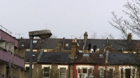 Two men climbed to the top of a roof during standoff with police in Kilburn. Picture:@jamesrobking