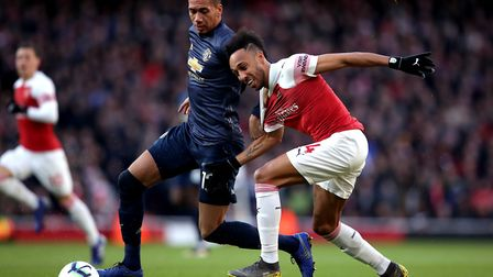 Arsenal's Pierre-Emerick Aubameyang (right) and Manchester United's Chris Smalling battle for the ba