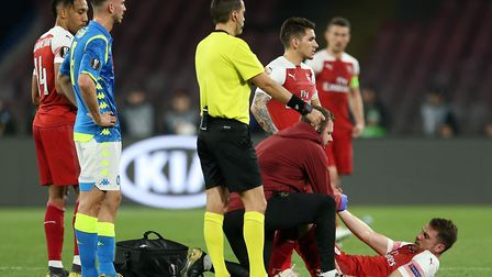 Arsenal's Aaron Ramsey receives treatment after picking up an injury during the UEFA Europa League q