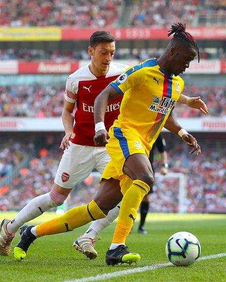 Arsenal's Mesut Ozil (left) and Crystal Palace's Wilfried Zaha battle for the ball (pic Bradley Coll